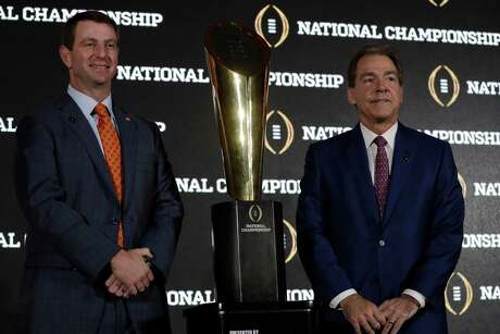 Clemson coach Dabo Swinney, left, and Alabama coach Nick Saban, who looks like he would rather be any place other than where is, share a little face time with the championship trophy that will go to the winner of the title game.