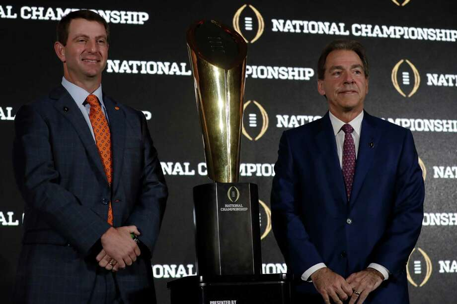 Clemson coach Dabo Swinney, left, and Alabama coach Nick Saban, who looks like he would rather be any place other than where is, share a little face time with the championship trophy that will go to the winner of the title game. Photo: Morry Gash, STF / Copyright 2017 The Associated Press. All rights reserved.