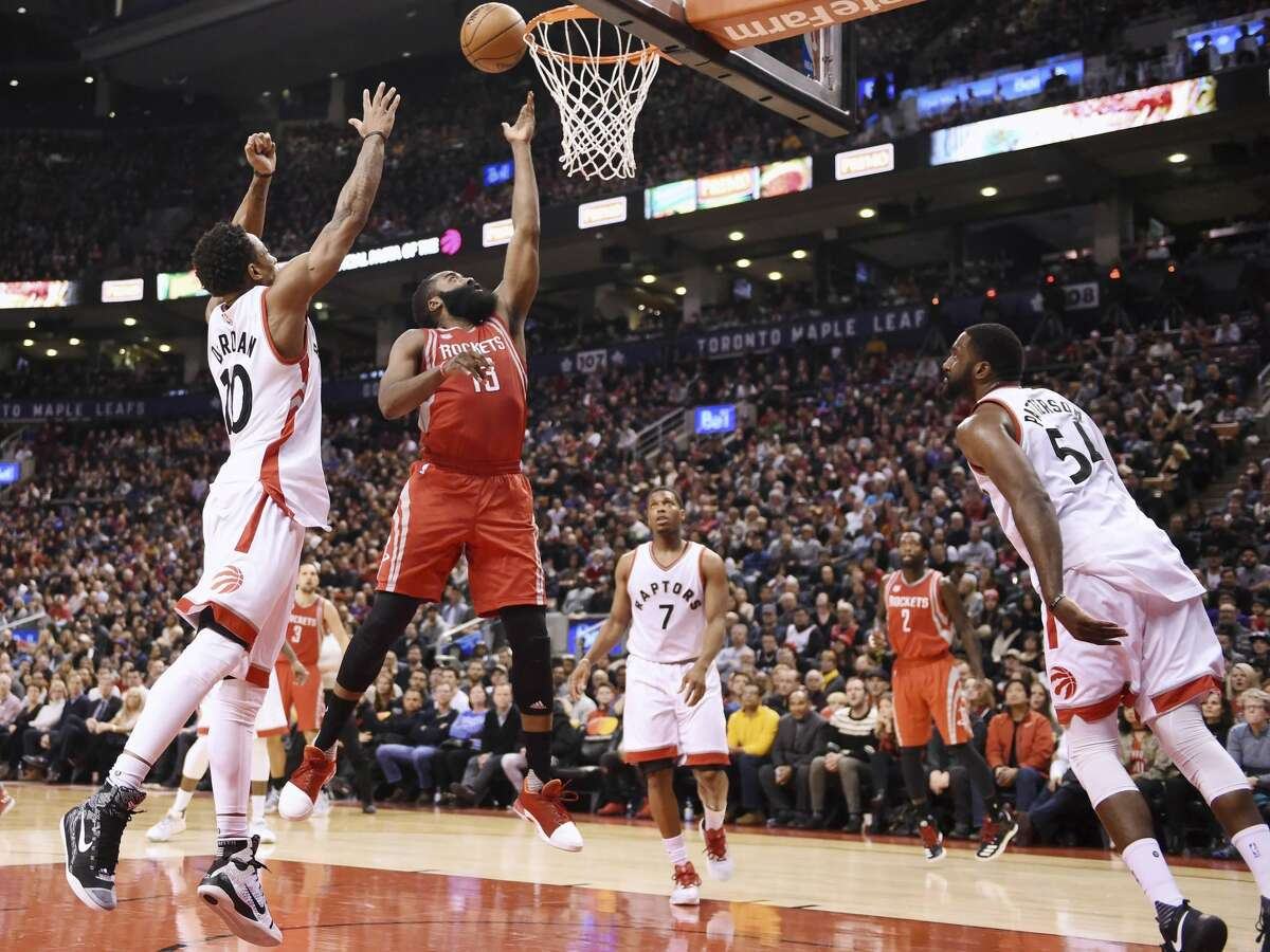 Houston Rockets guard James Harden (13) scores as Toronto Raptors guard DeMar DeRozan (10) defends and guard Kyle Lowry (7) and forward Patrick Patterson (54) look on during the second half of an NBA basketball game in Toronto on Sunday, Jan. 8, 2017. (Frank Gunn/The Canadian Press via AP)