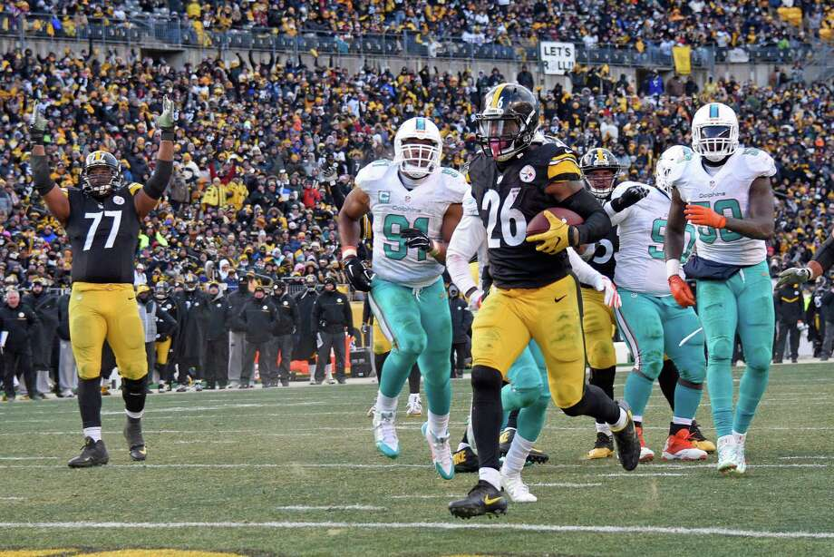 Steelers tackle Marcus Gilbert (77) makes the call as running back Le'Veon Bell (26) scores from 8 yards out in the third quarter of Sunday's AFC wild-card game at Pittsburgh. Bell rushed for 167 yards and two TDs. Photo: Don Wright, FRE / FR87040 AP