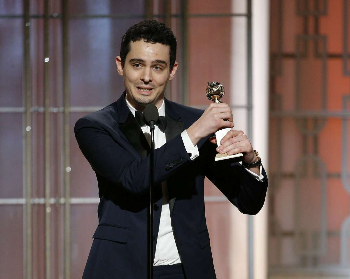 """This image released by NBC shows Damien Chazelle with the award for best screenplay for """"La La Land,"""" at the 74th Annual Golden Globe Awards at the Beverly Hilton Hotel in Beverly Hills, Calif., on Sunday, Jan. 8, 2017. (Paul Drinkwater/NBC via AP)"""