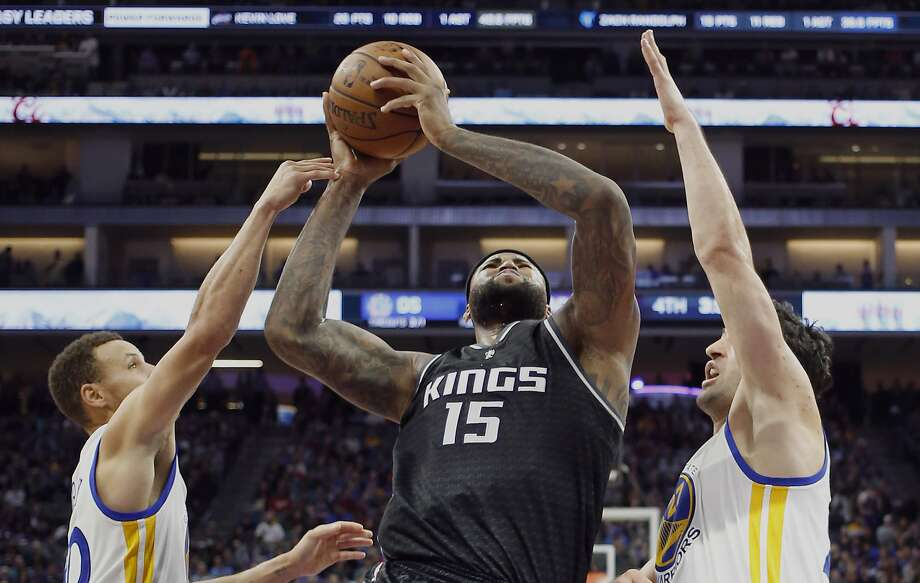 Sacramento Kings forward DeMarcus Cousins, center, goes to the basket between Golden State Warriors' Stephen Curry, left, and Zaza Pachulia during the second half of an NBA basketball game Sunday, Jan. 8, 2017, in Sacramento, Calif. The Warriors won 117-106. (AP Photo/Rich Pedroncelli) Photo: Rich Pedroncelli, Associated Press