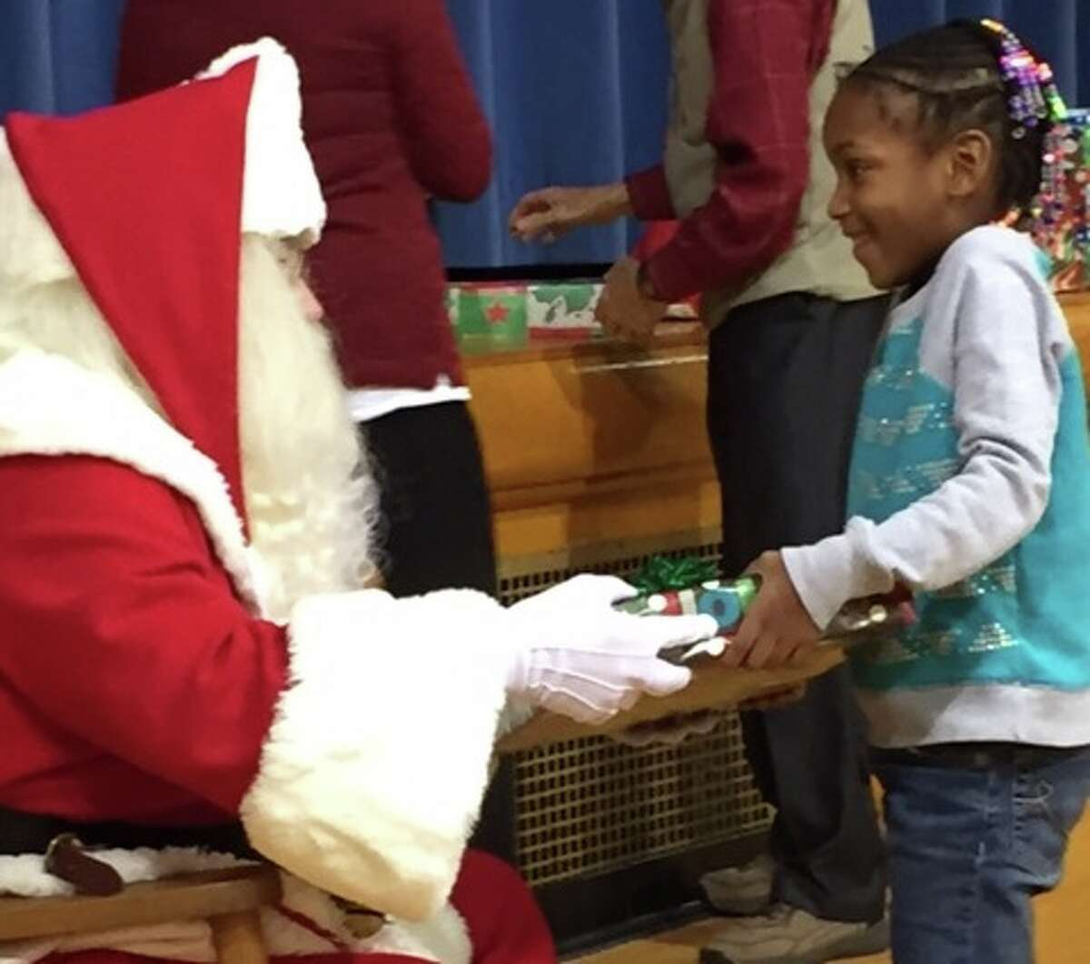 Santa offers a present to Eastlawn Elementary first-grader Oveeanna Montgomery.