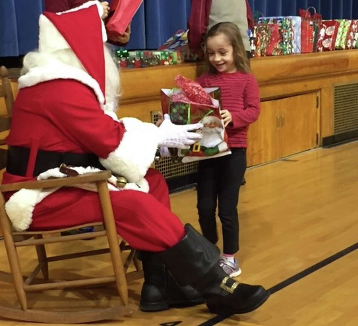 Santa offers a present to Eastlawn Elementary first-grader Taylor Marderness.