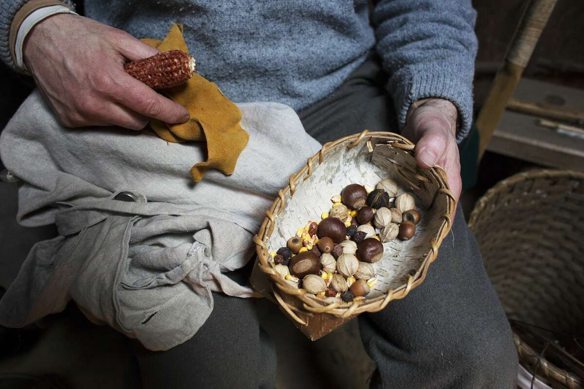 Kyle Bagnall, Manager of Historical Programs at the Chippewa Nature Center, handles a bowl made of birch bark and filled with nuts and seeds while teaching a