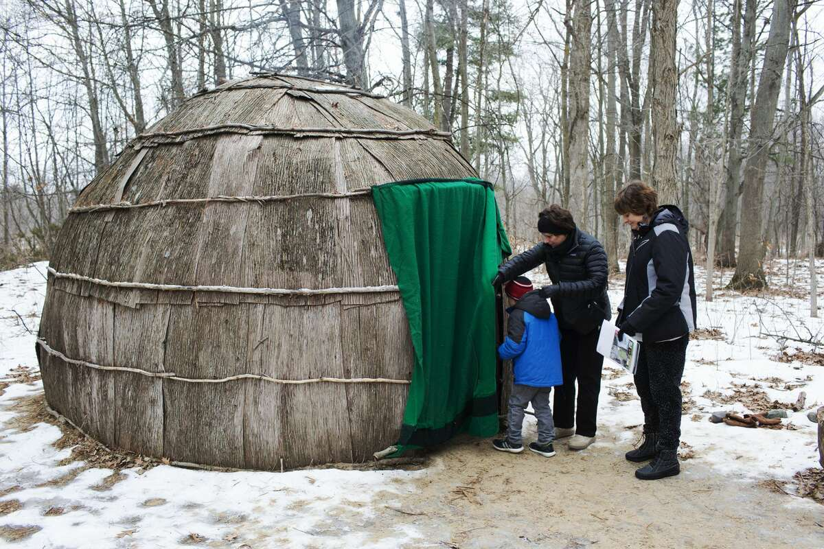 Denise House, of Essexville, assists Rowen House, 6, in to a Wigwam while with Beth Hargrove, of Bay City, during a