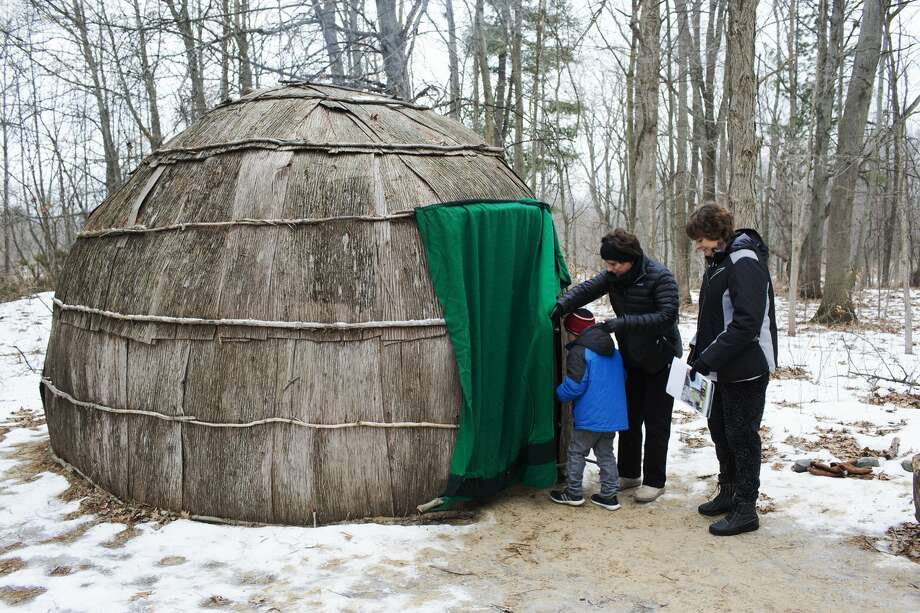 """Denise House, of Essexville, assists Rowen House, 6, in to a Wigwam while with Beth Hargrove, of Bay City, during a """"Wigwam in the Winter"""" program at the Chippewa Nature Center on Sunday. Photo: THEOPHIL SYSLO 
