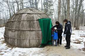 """Denise House, of Essexville, assists Rowen House, 6, in to a Wigwam while with Beth Hargrove, of Bay City, during a """"Wigwam in the Winter"""" program at the Chippewa Nature Center on Sunday."""