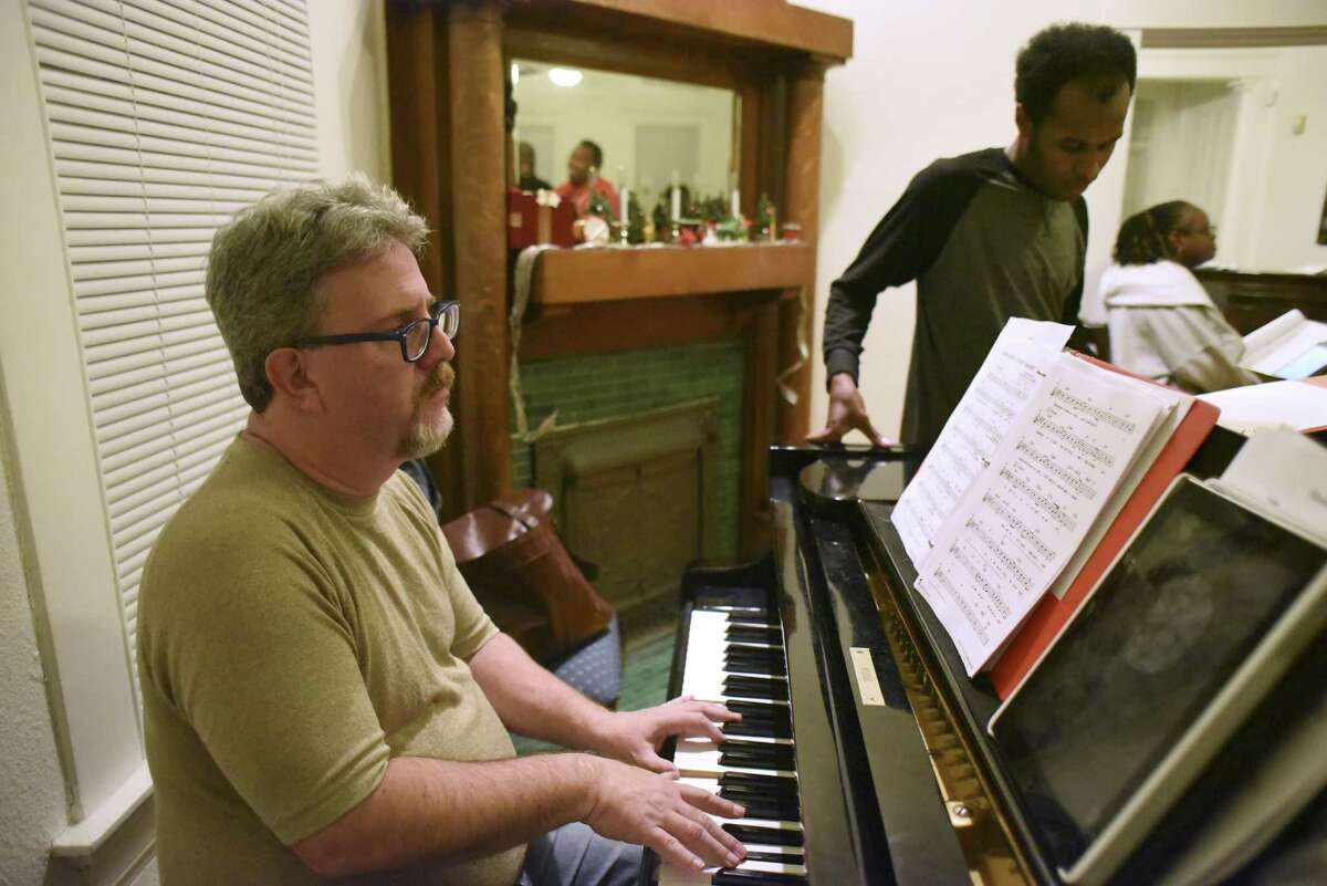 Darrin Newhardt. playing piano during a rehearsal, is director and music director of