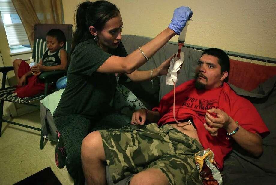 Patricia Martinez, center, administers medication to her disabled husband Jerry, right. Photo: Bob Owen, Staff / San Antonio Express-News / San Antonio Express-News