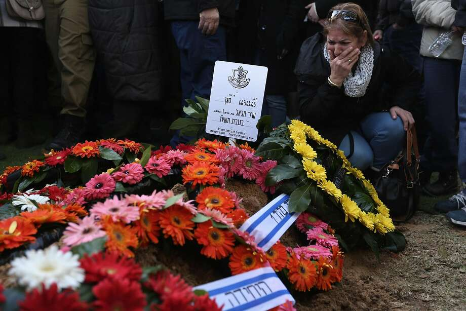 A relative of Israeli soldier Shir Hajaj, 22, mourns over her grave at a military cemetery in Jerusalem. Photo: MENAHEM KAHANA, AFP/Getty Images