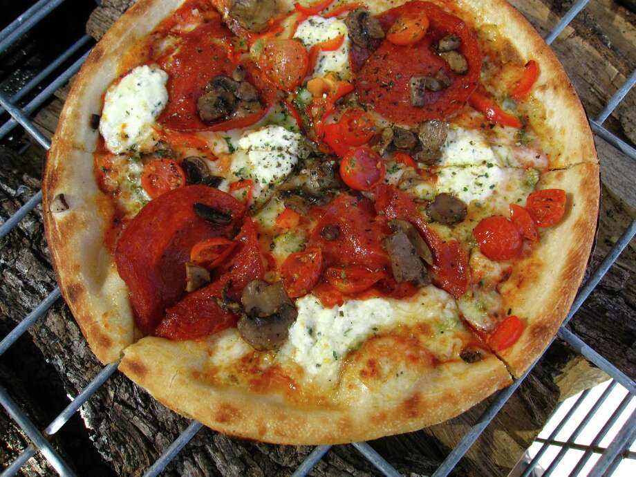 The new Quicky Wood Fired Pizza on Fredericksburg Road lets customers pick the ingredients on their pizzas for a flat $8.99 price. Then they cook it in a wood-burning oven. This one includes mozzarella and ricotta cheeses, garlic, basil pesto, red peppers, pepperoni, mushrooms and tomatoes. Photo: Mike Sutter /San Antonio Express-News