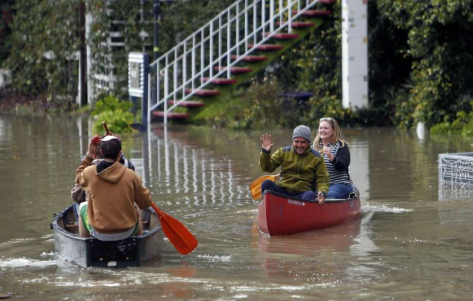 Marz Khoeayari waves as he gets a ride with Kayte Guglielmino in her canoe as Russian River floodwaters cover Old River Road in Guerneville, Calif., on Monday, January 9, 2017. Photo: Scott Strazzante, The Chronicle