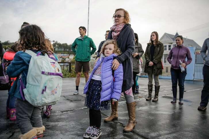 Aoife O'Dwyer, 7 (center), rests on her mother Kendra O'Dwyer as she waits in line before entering school in San Francisco, Calif., on Monday, Jan. 9, 2017.