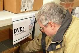 Albert Teplica of Rowayton finds some favorite films at the Darien Library's annual Mid-Winter Book Sale, Saturday, Jan. 7, 2017, in Darien, Conn.