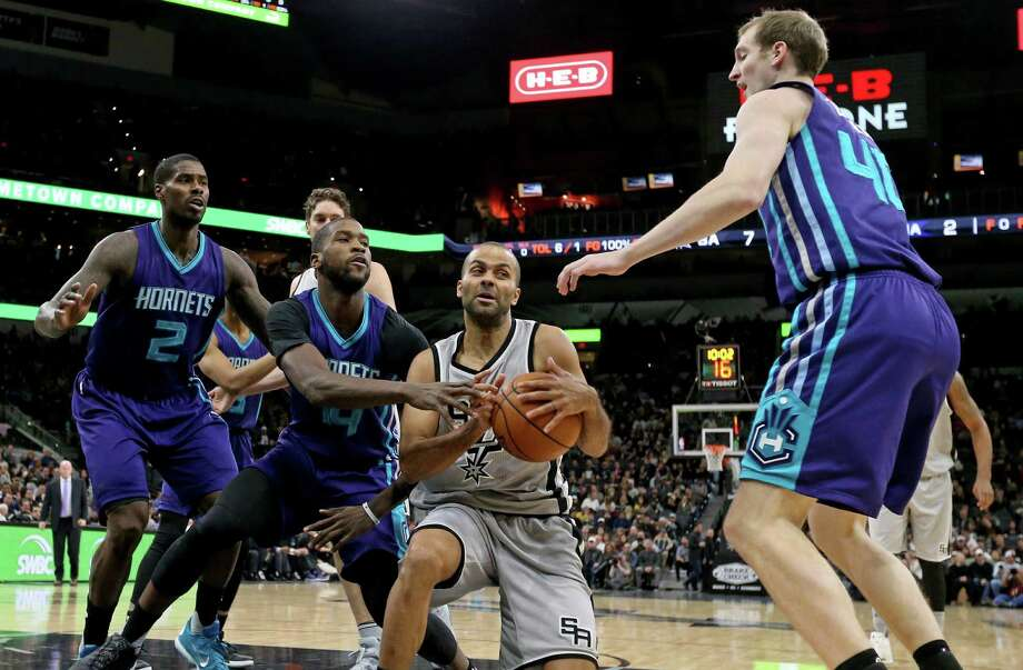 Spurs' Tony Parker looks for room between Charlotte Hornets' Marvin Williams (from left), Michael Kidd-Gilchrist and Cody Zeller during first half action on Jan. 7, 2017 at the AT&T Center. Photo: Edward A. Ornelas /San Antonio Express-News / © 2017 San Antonio Express-News