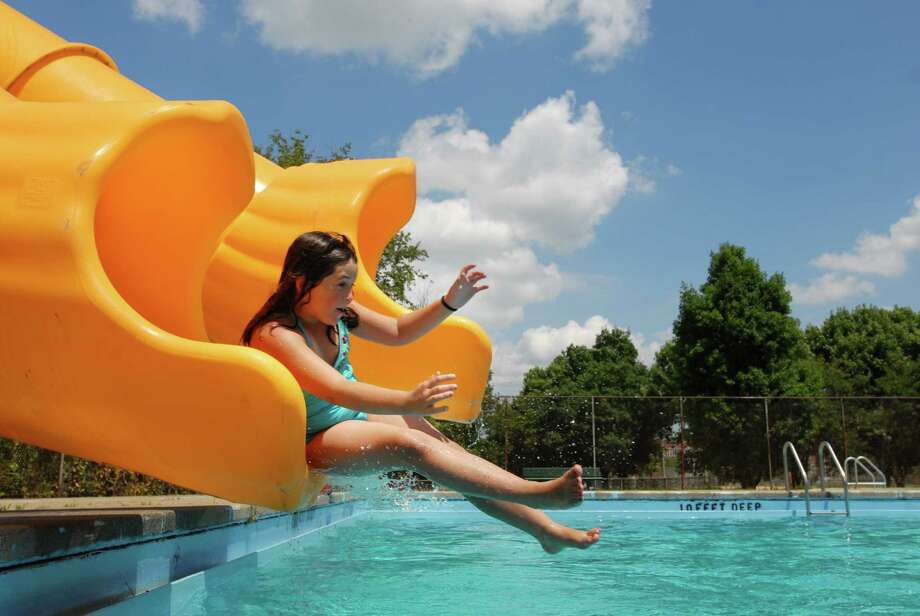 Brionna Davey, age 11 of Lansingburgh, slides into the Knickerbacker Park Pool during opening day for Lansingburgh swimming facility, Friday July 9, 2010. (Will Waldron / Times Union) Photo: Ww / 00009464A