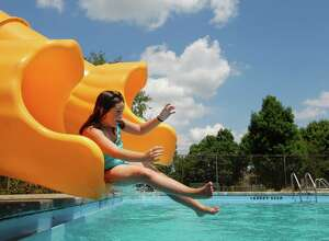 Brionna Davey, age 11 of Lansingburgh, slides into the Knickerbacker Park Pool during opening day for Lansingburgh swimming facility, Friday July 9, 2010. (Will Waldron / Times Union)
