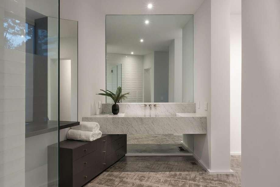 Carrera marble fashions a striking vanity in the spa caliber master bathroom. Photo: Rebecca Kmiec