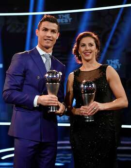 Real Madrid and Portugal's forward and winner of The Best FIFA Mens Player of 2016 Award Cristiano Ronaldo stands on stage with Houston Dash and US midfielder and winner of The Best FIFA Womens Player of 2016 Carli Lloyd following The Best FIFA Football Awards 2016 ceremony, on January 9, 2017 in Zurich. / AFP PHOTO / Fabrice COFFRINIFABRICE COFFRINI/AFP/Getty Images