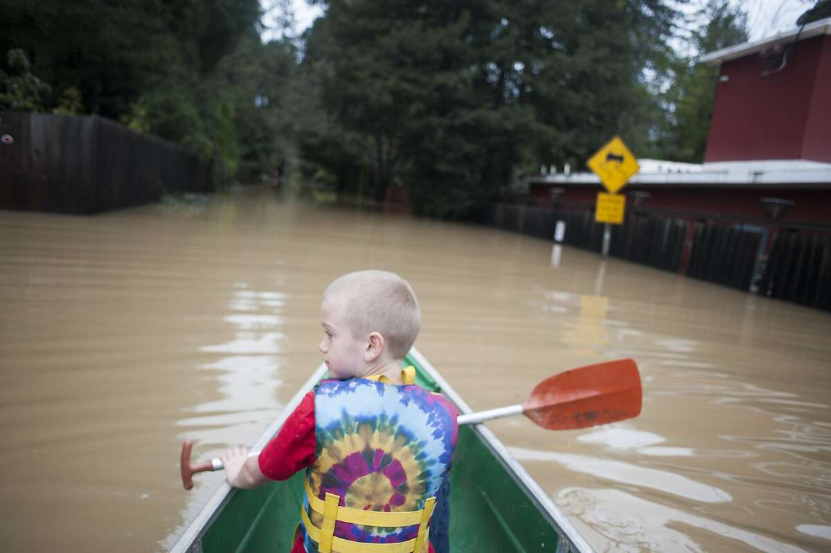 8-year-old son Hendrix Robinson crossed flooded waters on Neeley Road during flooding in Guerneville, CA on January 9, 2017. Hendrix is a third grader at the Forestville School, which was closed for the day due to flooding.