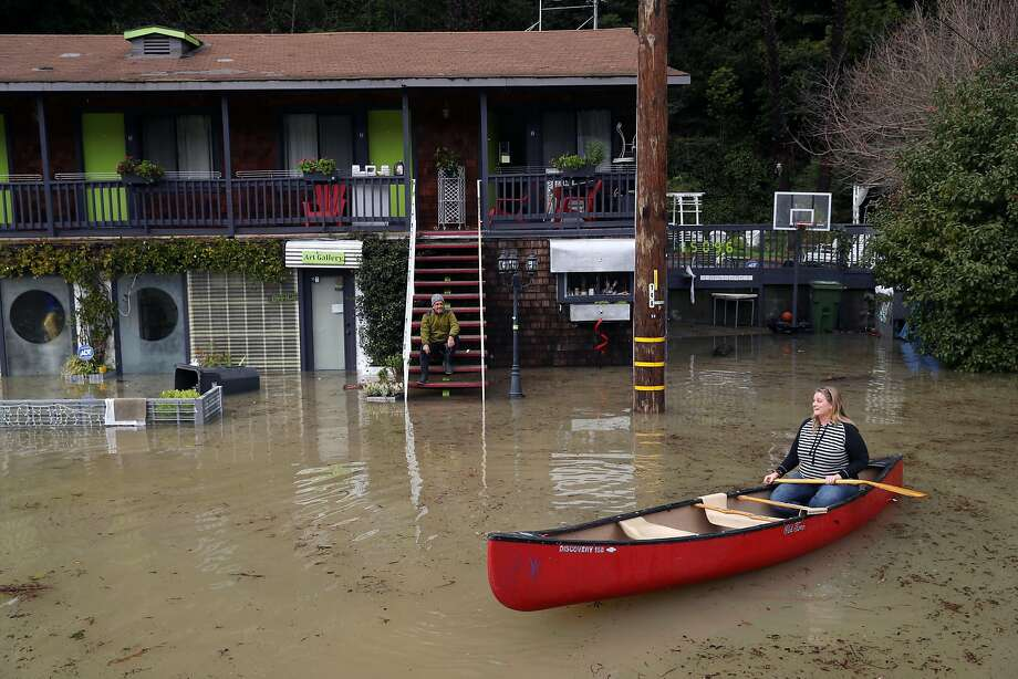 Russian River Studios owner Marz Khoeayari sits on his steps as nearby resident Kayte Guglielmino surveys the scene from her canoe on Old River Road as Russian River crests over flood level in Guerneville, Calif., on Monday, January 9, 2017. Photo: Scott Strazzante, The Chronicle