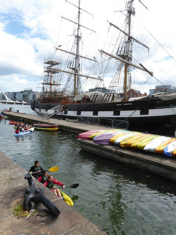 Kayakers pull into port near where the tall ship Jeanie Johnson is tied up along the River Liffey in Dublin, Ireland.