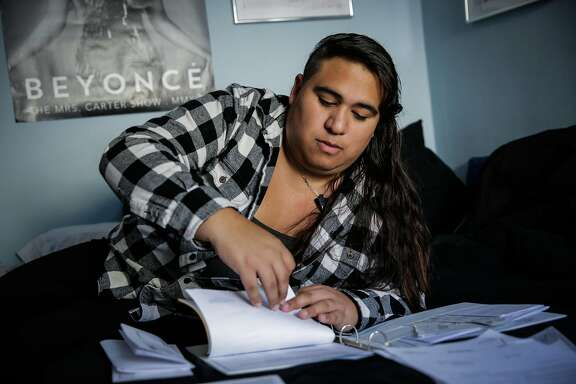 Lexi Adsit goes through the paperwork she has to complete to change the gender markers on her identification documents, at her home in San Leandro, Calif., on Tuesday, Dec. 27, 2016.