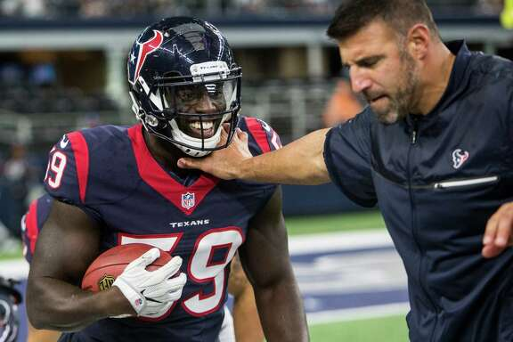 Texans linebacker Whitney Mercilus, left, enjoys a lighter moment with Mike Vrabel, his position coach, before a game this season.