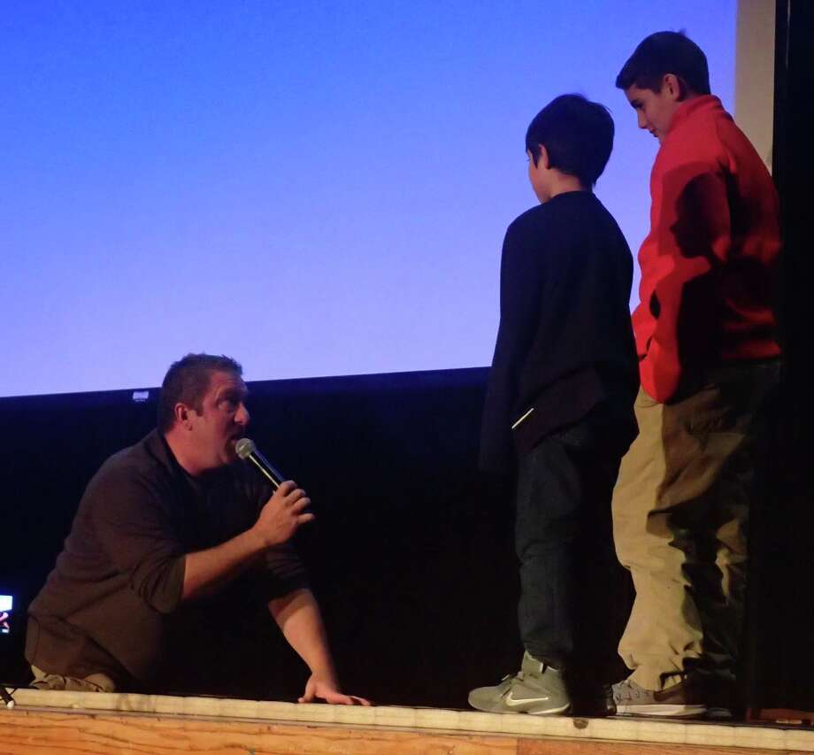 Motivational speaker Dave Stevens, left, gets ready to demonstrate to Danbury Youth Wrestling Association members Sean Donovan, right, and Anthony Valenzuela how he was able to foil the best efforts of opposing blockers as a nose guard on his high school and college football teams despite being born without legs. Stevens gave a presentation to an audience of several hundred at the Danbury High School auditorium Jan. 9, 2017. Photo: Richard Gregory / Richard Gregory