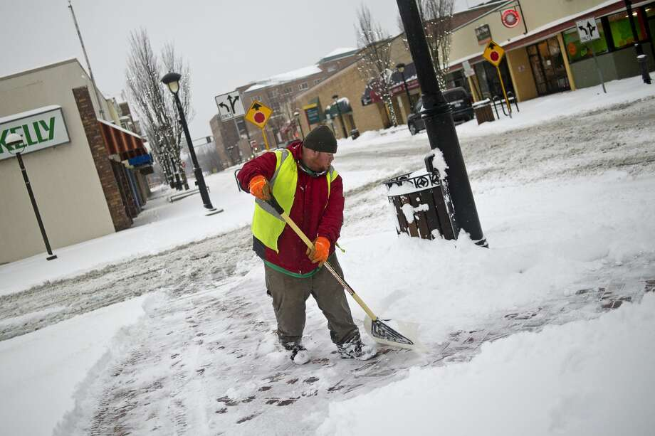 City of Midland seasonal employee Al Conrad works to clear the intersection of Ashman Street and Larkin Street on Tuesday morning in downtown Midland. Roughly six inches of snow fell overnight and will continue throughout the morning before turning into rain this afternoon. Conrad said he and fellow employee TJ Feinauer started just after 7 a.m. Photo: Erin Kirkland/Midland Daily News
