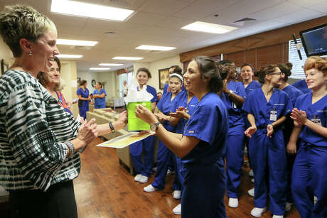 "Natalie Rodriguez, a senior at Health Careers High School, receives a prize for naming the CHRISTUS Santa Rosa Physicians Ambulatory Surgery Center's da Vinci Xi surgical robot ""Leonardo"" from physicians relations manager Christa Franklin (left) on Wednesday, Oct. 5, 2016.  Students from the school learned how to operate the robot, which uses video game-like technology to perform surgeries.  Surgeons set up at a console with a video and fingerholds and a robot performs  on the patient by mimicking the sugeon's virtual movements.  MARVIN PFEIFFER/ mpfeiffer@express-news.net"