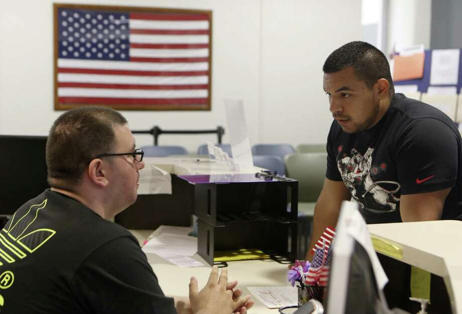 Jacob Salazar, a student aid at the Veterans Affairs office at San Antonio College answers questions about class scheduling for former Marine Corporal Rito Adame. Adame is using his GI Benefits to pay for his associates degree in Criminal Justice and hopes to become a San Antonio police officer. Photo: Helen L. Montoya /San Antonio Express-News / ©2014 San Antonio Express-News
