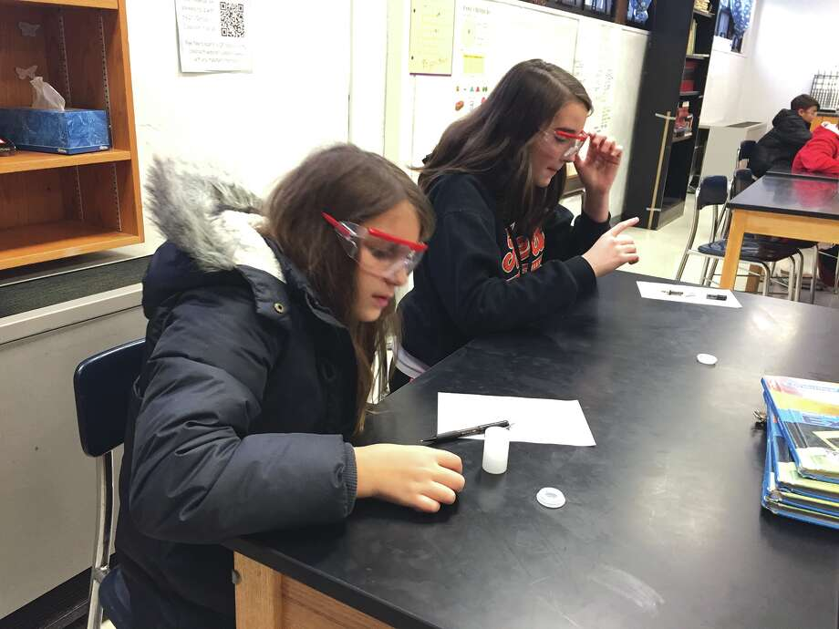 Lincoln Middle School seventh graders Jordan Baer, left, and Bailey Schuetz let their Alka-Seltzer tablets dissolve in a film canister. Photo: Julia Biggs • Intelligencer