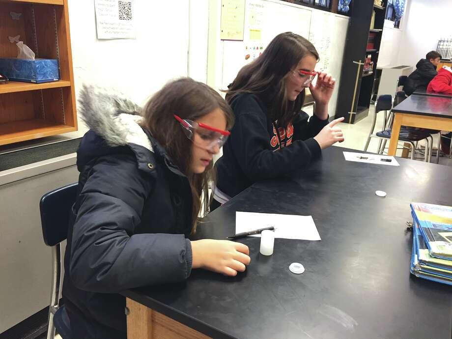 Lincoln Middle School seventh graders JordanBaer, left, and BaileySchuetz let their Alka-Seltzer tablets dissolve in a film canister. Photo: Julia Biggs • Intelligencer