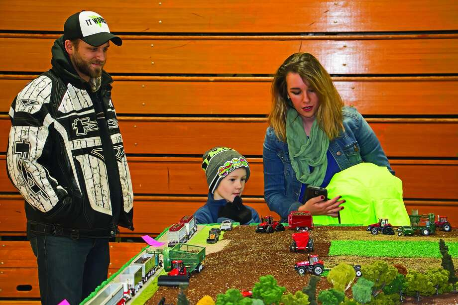 David and Sheree Gorkowski and their son, Bentley, of Bad Axe, look over one of the displays at the Annual FFA Toy Tractor Show at Laker Schools on Saturday. Photo: Bill Diller/For The Tribune
