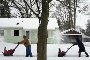 """BRITTNEY LOHMILLER   blohmiller@mdn.net Jeff Ropp, left, and Katie Kole, both of Midland, snow blow the sidewalk in front of Kole's home Tuesday afternoon in Midland. """"I live across the street but came over to help,"""" Ropp said. Approximately six inches of snow fell overnight and continued throughout the morning before turning into rain this afternoon. A light glaze of ice will be possible on snow as this transition occurs, according to the National Weather Service in Detroit. South to southwest wind gusts are expected to increase to around 40 mph during the mid afternoon hours today. Winds will switch to the southwest this evening with wind gusts increasing and ranging between 40 and 50 mph."""