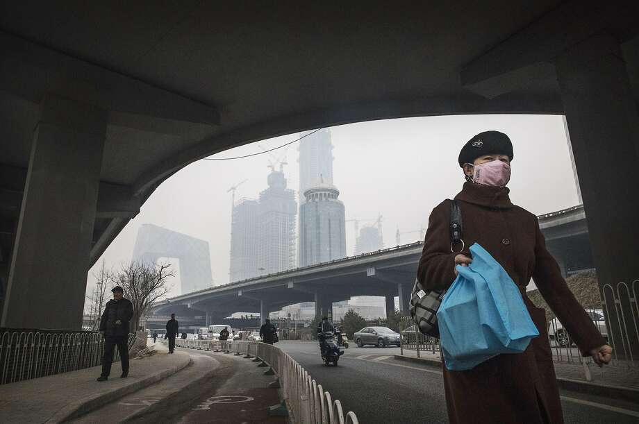 A Chinese woman wears a mask as she walks down a street on a polluted day in Beijing last month. Photo: Kevin Frayer, Getty Images