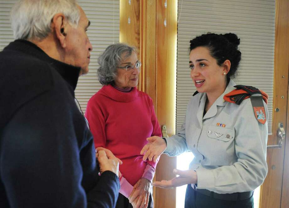 Israel Defense Forces soldier, Captain Heli, right, 26, chats with Greenwich residents Sohier and Elaine Marks, after speaking at Temple Sholom in Greenwich, Conn. Tuesday, Jan. 10, 2017. Four active duty IDF soldiers spoke about their roles in the service, specific missions they took part in, and addressed the political climate and current events in Israel. Photo: Tyler Sizemore / Hearst Connecticut Media / Greenwich Time