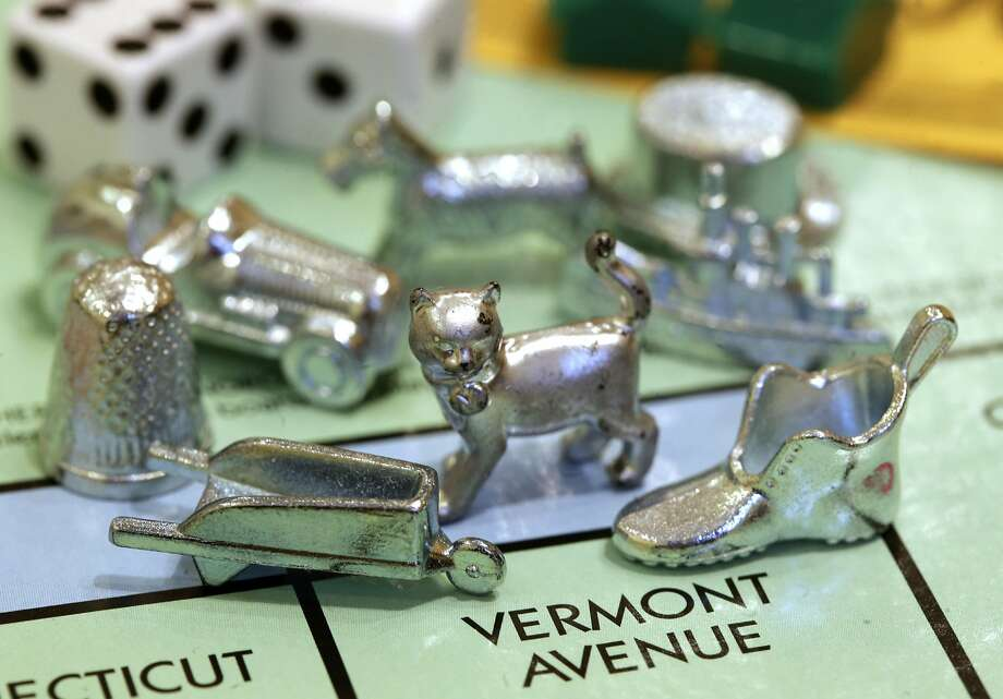 A cat, a newer Monopoly token, rests on a Boardwalk deed next to other tokens still in use, including the wheelbarrow and the shoe at Hasbro Inc. headquarters in Pawtucket, R.I. Voting on Facebook determined that the cat would replace the iron token in 2013. Photo: Steven Senne, Associated Press