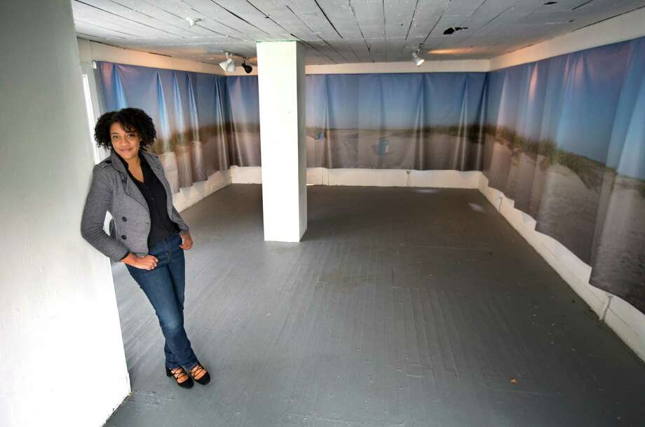 Artist Regina Agu with her piece Sargassum currently hanging at Project Row Houses, Wednesday, Jan. 4, 2017, in Houston. The installation features a giant canvas photograph showing an artificial beach in Galveston. It also features snippets of poems hanging on the wall.( Mark Mulligan / Houston Chronicle ) Photo: Mark Mulligan, Staff / © 2017 Houston Chronicle