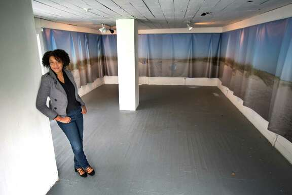 Artist Regina Agu with her piece Sargassum currently hanging at Project Row Houses, Wednesday, Jan. 4, 2017, in Houston. The installation features a giant canvas photograph showing an artificial beach in Galveston. It also features snippets of poems hanging on the wall.( Mark Mulligan / Houston Chronicle )