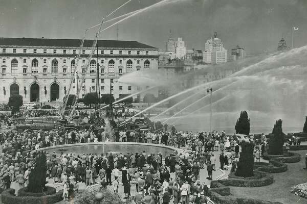 September 14, 1950: From the back of the photo -  Water power -- Several thousand visiting firemen watched with professional eyes a spectacular demonstration of fire fighting techniques in the Civic Center plaza. Water towers, aerial trucks and several types of ground hoses, provided by the San Francisco Fire Department, sprayed 750 gallons of water a minute for their benefit. The visitors were members of the International Association of Fire Chiefs, here for their 77th annual conference. The display was supervised by Chief Edward Walsh and First Assistant Chief George Trapp.