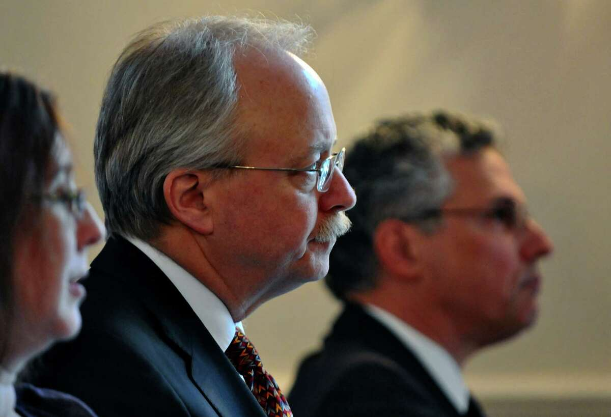 Robert Ward, Deputy Director of the institute, center, and Thomas Gais, Director of the Nelson A. Rockefeller Institute of Government, right, listen to City of Rochester Mayor Thomas Richards speak during a public policy forum titled
