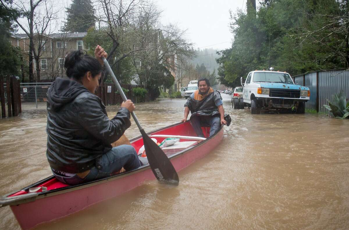Luis, left, and Samuel Sanchez make their way home through the flooded streets of Guerneville, Calif. Tuesday, January 10, 2017. Major winter storms drenched much of the bay area leaving some of it flooded.