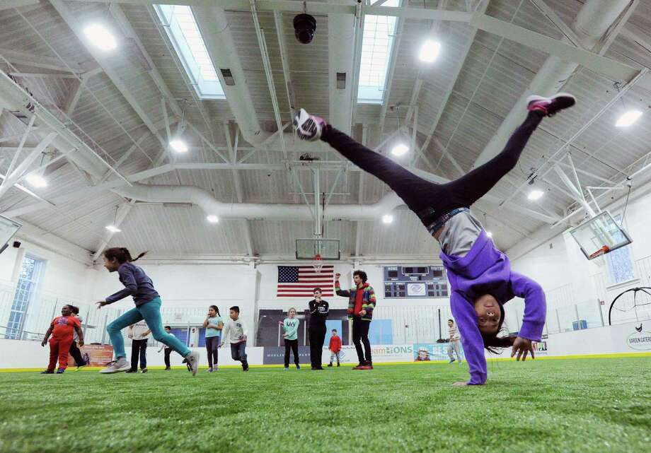 Club member Fernanda Perez, 10, right, takes advantage of the new turf field to demonstrate a gymnastics move in the field house at the Boys & Girls Club of Greenwich. Photo: Bob Luckey Jr. / Hearst Connecticut Media / Greenwich Time