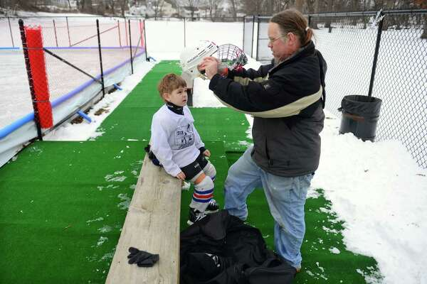 Liam Scheck, 6, of Stratford, gets help with his hockey helmet from dad Mark, at Longbrook Park Ice Rink in Stratford, Conn., on Tuesday Jan. 10, 2017.
