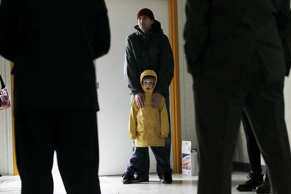 Mc Allen (top center), Dogpatch Neighborhood Association member, stands with his son Lincoln (bottom center), 4, as they listen to Mayor Ed Lee (left), address those gathered at the site of a new Navigation Center in the Dogpatch neighborhood during a press conference on Tuesday, January 10,  2017 in San Francisco, Calif.