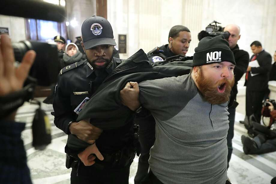 "WASHINGTON, DC - JANUARY 10:  A protester shouts, ""No Trump, No KKK, No facist USA"" as he is hauled out of the Senate Judiciary Committee's confirmation hearing for Sen. Jeff Sessions (R-AL) to be the next U.S. Attorney General in the Russell Senate Office Building on Capitol Hill January 10, 2017 in Washington, DC. Sessions was one of the first members of Congress to endorse and support President-elect Donald Trump, who nominated him for Attorney General.  (Photo by Chip Somodevilla/Getty Images) Photo: Chip Somodevilla, Getty Images"