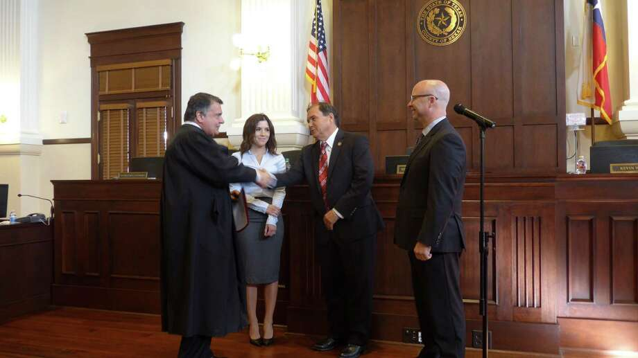 """U.S. District Judge Orlando Garcia, left, swears in Precinct 3 Commissioner Kevin Wolff, right, and Precinct 1 Commissioner Sergio """"Chico"""" Rodriguez, accompanied by his daughter, Liana. Wolff and Rodriguez were re-elected Nov. 8 to new four-year terms. Photo: John W. Gonzalez / San Antonio Express-News Staff"""
